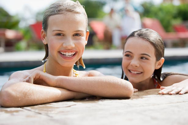 two girls leaning on the edge of pool, smiling