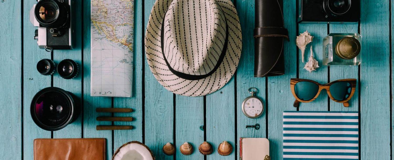 hat, map, sunglasses, shells on table