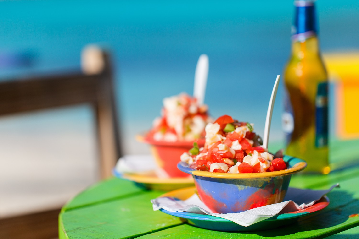 Two bowls of Bahamian conch salad and bottle of beer