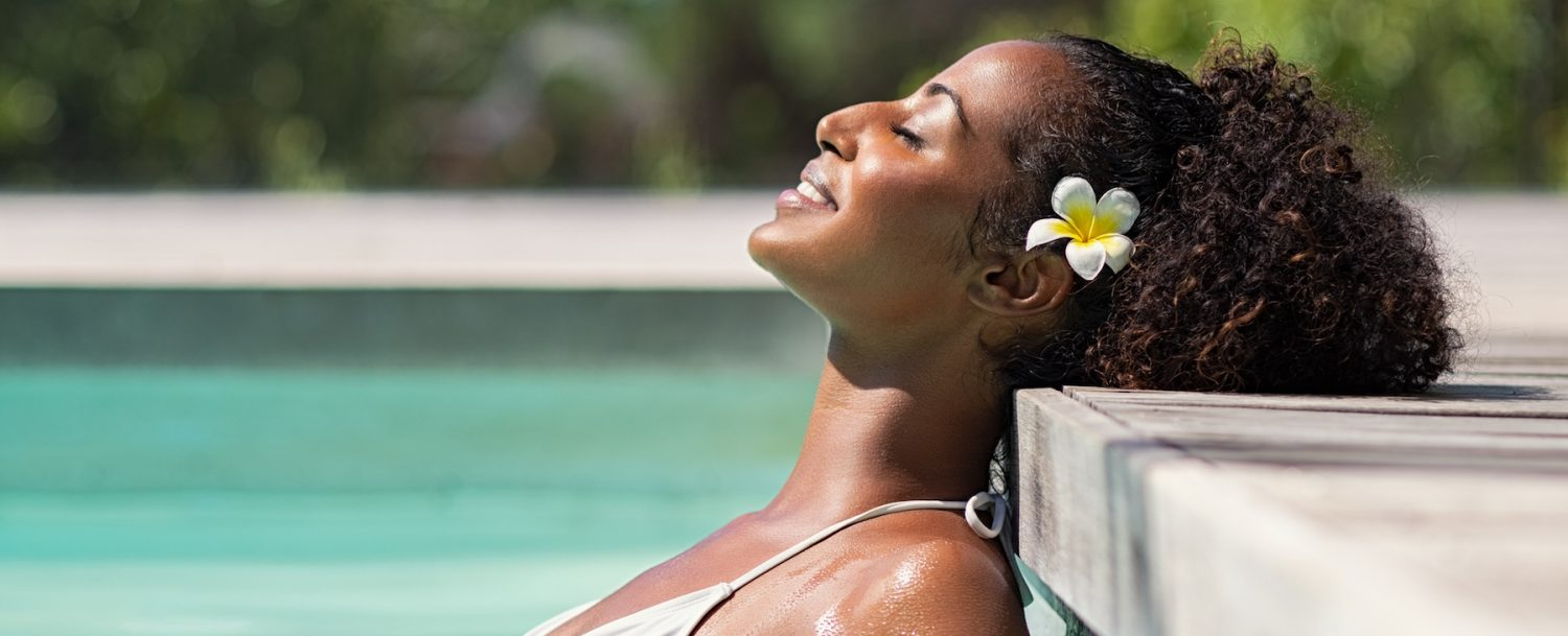 Young black woman relaxing at spa pool with frangipane flower in the hair. Beautiful young woman relaxing in outdoor spa swimming pool with head leaning at poolside. Closeup face of attractive black girl with closed eyes enjoy vacation at resort. (You